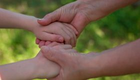 The hands of an adult hold the hands of a child.