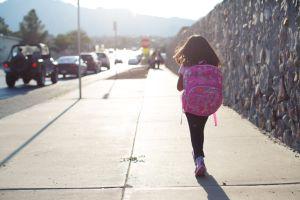 Girl Walking To School Along Busy Street