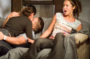 Young woman uncomfortable beside couple passionately kissing on couch