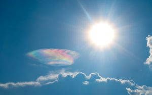 Beautiful Iridescent clouds appear on the sky nearly the sun.