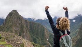 Woman in Machu Picchu celebrating reaching the top of a mountain