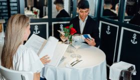 Young man and woman read the menu in a fancy restaurant.