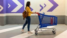 Young woman pushing an empty shopping cart in the supermarket garage.