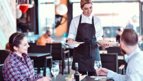 Smiling Waitress Bringing Dinner To Happy Couple