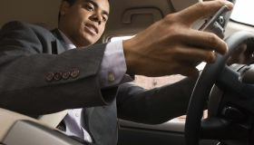 Businessman using cell phone while driving
