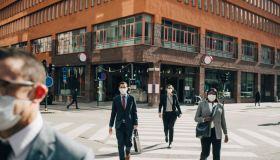 Male and female entrepreneurs crossing street on sunny day in city during pandemic
