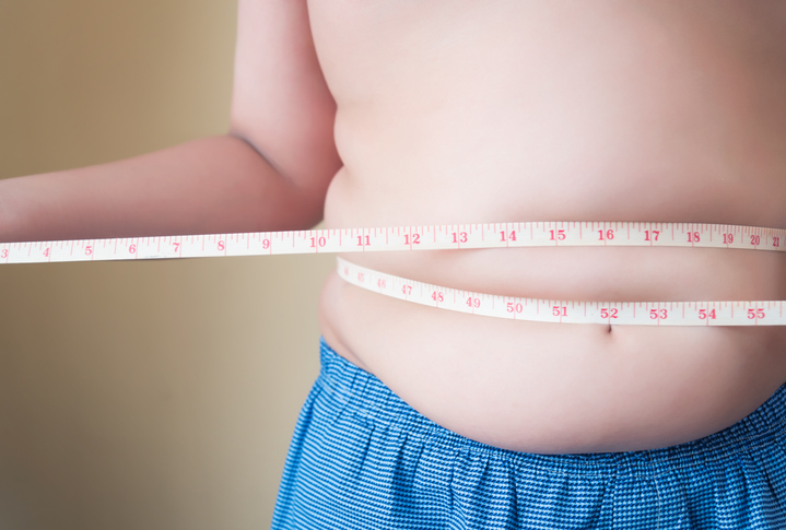 Midsection Of Overweight Boy Measuring Waist With Tape While Standing Against Wall