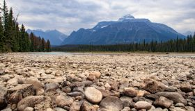 Pebbles in foreground of river bank in dramatic Canadian landscape of Jasper national Park